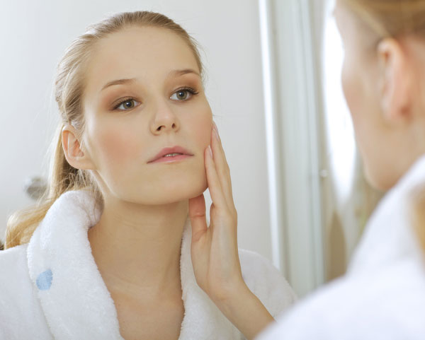A woman is seeing her reflection in a mirror while holding her right cheek