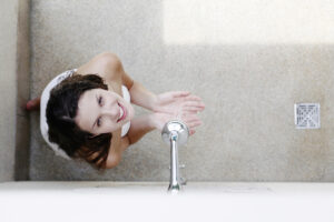 A woman having a hot shower in the bathroom